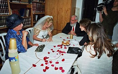 Nathalie Lastreger signing her ketubba (marriage contract) ahead of her 2004 Conservative unreported private wedding ceremony. (courtesy)