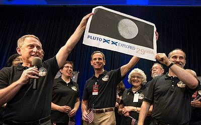In this photo provided by NASA, New Horizons Principal Investigator Alan Stern of Southwest Research Institute (SwRI), Boulder, Colo., left, Johns Hopkins University Applied Physics Laboratory (APL) Director Ralph Semmel, center, and New Horizons Co-Investigator Will Grundy of the Lowell Observatory hold a print of a US stamp with their suggested update since the New Horizons spacecraft made its closest approach to Pluto, at the Johns Hopkins University Applied Physics Laboratory (APL) in Laurel, Md. on Tuesday, July 14, 2015. (Bill Ingalls/NASA via AP)