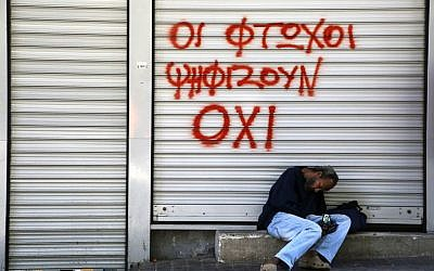 "A man sleeps, holding an icon of Jesus Christ, outside a closed shop with spray paint reading ""Poor vote ""NO"" in central Athens, on Saturday, July 4, 2015. (AP/Petros Karadjias)"