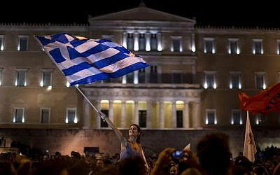 A supporter of the No vote waves a Greek flag in front of the parliament after the results of the referendum at Syntagma square in Athens, Sunday, July 5, 2015. (AP/Emilio Morenatti)