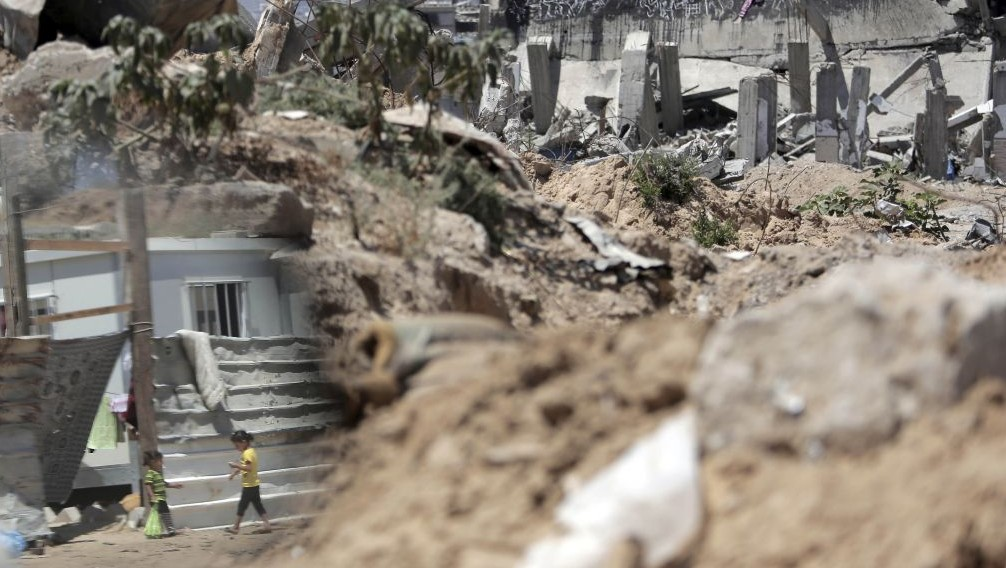 In this June 17, 2015 photo, Palestinian girls are seen reflected in a mirror as they walk next to rubble in the area where they live with family after losing their house in Gaza City. (AP/Khalil Hamra)
