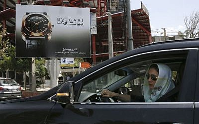 A woman drives in front of an advertising billboard for Bulgari watches in northern Tehran, Iran, Saturday, July 18, 2015. (AP/Vahid Salemi)