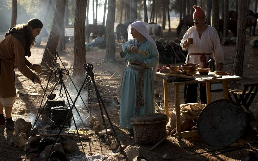 Israeli and Russian members of knight clubs cook their breakfast before the reenactment of the Battle of Hattin in Lavi Forest, northern Israel, July 4, 2015. (AP/Oded Balilty)