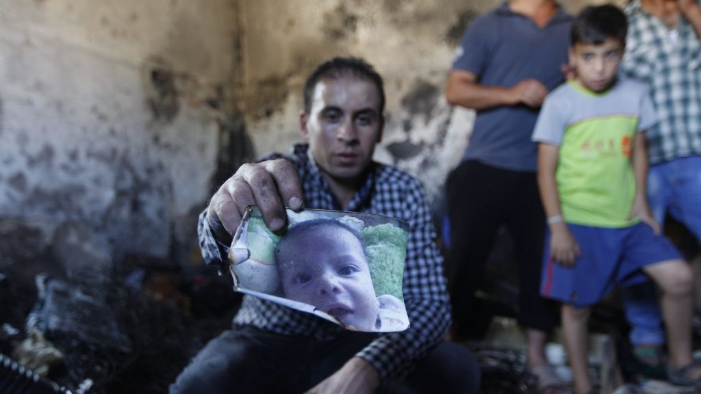 A relative holds up a photo of a one-and-a-half year old boy, Ali Dawabsha, in the family house torched in a suspected attack by Jewish terrorists in Duma village near the West Bank city of Nablus, Friday, July 31, 2015. The boy died in the fire, his parents, badly hurt, also later died. (AP Photo/Majdi Mohammed)