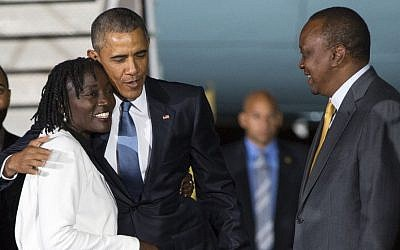 Kenyan President Uhuru Kenyatta, right, watches as President Barack Obama, center, hugs his half-sister Auma Obama, after he arrived at Kenyatta International Airport, on Friday, July 24, 2015, in Nairobi, Kenya (AP Photo/Evan Vucci)