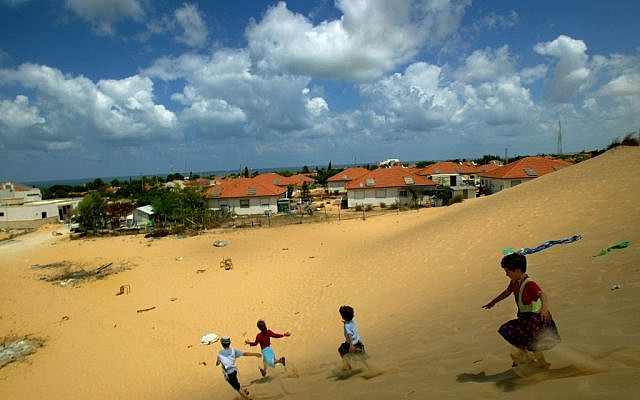 Israeli children play on a sand dune overlooking their homes in the Jewish settlement of Neve Dekalim, in the Gush Katif bloc in the southern Gaza Strip, Monday, Aug. 8, 2005. N (AP Photo/David Guttenfelder)