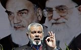 Hamas then political leader Ismail Haniyeh delivers a speech in front of portraits of late Iranian revolutionary founder Ayatollah Khomeini (left), and supreme leader Ayatollah Ali Khamenei (right), at a rally in Tehran, February 11, 2012. (AP/Vahid Salemi)