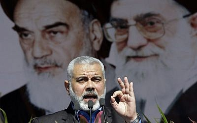 Former Hamas prime minister Ismail Haniyeh delivers a speech in front of portraits of late Iranian revolutionary founder Ayatollah Khomeini (left), and supreme leader Ayatollah Ali Khamenei (right), at a rally in Tehran, February 11, 2012. (AP/Vahid Salemi)
