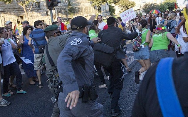 Security forces reach for an ultra-Orthodox Jew attacking people with a knife during a Gay Pride parade Thursday, July 30, 2015 in central Jerusalem. (AP Photo/Sebastian Scheiner)