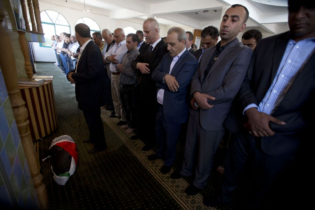Palestinian Prime Minister Rami Hamdallah, front, prays over the body of one-and-a-half year old boy, Ali Dawabsheh, during his funeral in Duma village near the West Bank city of Nablus, Friday, July 31, 2015. The toddler was burned to death when suspected Jewish assailants set fire to two Palestinian homes in the West Bank village early Friday. (AP Photo/Majdi Mohammed)