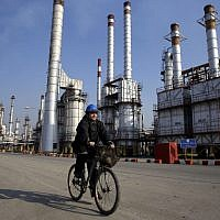 An Iranian oil worker rides his bicycle near an oil refinery south of the capital, Tehran, December 22, 2014. (AP/Vahid Salemi/File)