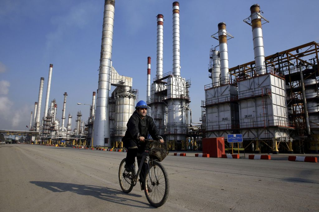 An Iranian oil worker rides his bicycle near an oil refinery south of the capital, Tehran, December 22, 2014. (AP/Vahid Salemi)