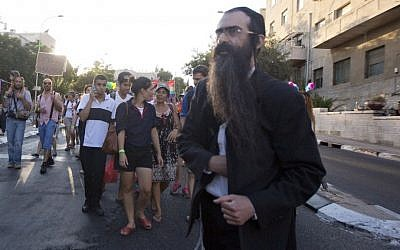 Yishai Schlissel pictured as he walks through a Gay Pride parade and is just about to pull a knife from under his coat and start stabbing people in Jerusalem, Thursday, July 30, 2015. (AP Photo/Sebastian Scheiner)