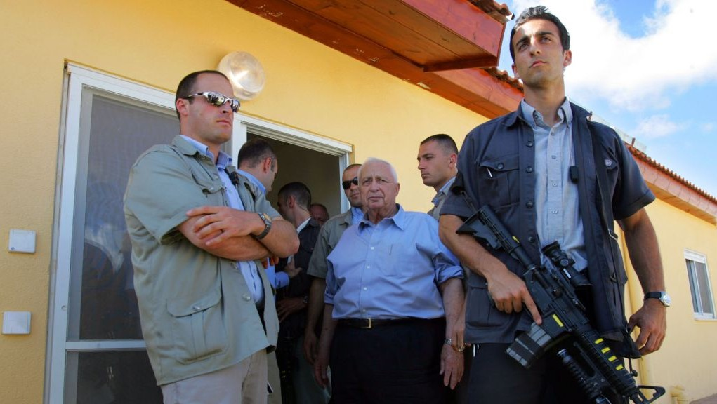 In this July 5, 2005 photo, prime minister Ariel Sharon, surrounded by his bodyguards, inspects temporary housing being built for settlers about to be evacuated from the Gaza Strip under his disengagement plan at the Nitzanim construction site in southern Israel. (AP Photo/David Silverman, Pool, File)
