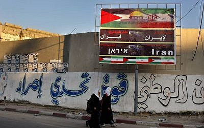 Palestinian school girls pass a billboard covered by national and Iranian flags with Arabic reading 'thanks and gratitude to Iran,' in Gaza City, November 28, 2012 (AP/Adel Hana)