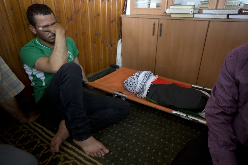 A Palestinian man mourns alongside the body of a one-and-a-half year old boy, Ali Dawabsha, during his funeral in Duma village near the West Bank city of Nablus, Friday, July 31, 2015. (Majdi Mohammed/AP)