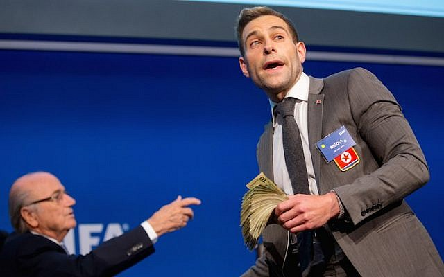 Comedian Simon Brodkin prepares to attack FIFA President Joseph S. Blatter (R) with money during a press conference at the Extraordinary FIFA Executive Committee Meeting at the FIFA headquarters on July 20, 2015 in Zurich, Switzerland. (JTA/Philipp Schmidli/Getty Images)
