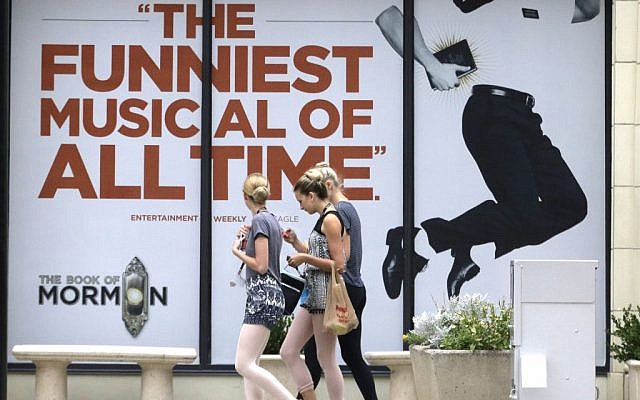 """People walk past signs announcing the """"Book of Mormon"""" musical at the Capitol Theatre, Monday, July 27, 2015, in Salt Lake City. (AP Photo/Rick Bowmer)"""