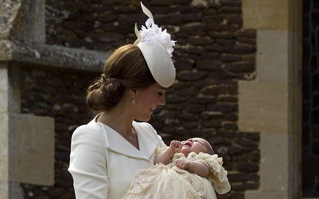 Britain's Kate the Duchess of Cambridge carries Princess Charlotte after taking her out of a pram as they arrive for Charlotte's Christening at St. Mary Magdalene Church in Sandringham, England, Sunday, July 5, 2015. (AP/Matt Dunham, Pool)