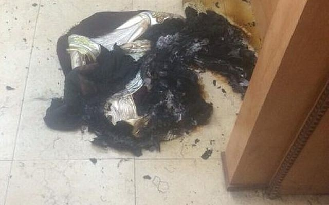 The curtain from an ark in a central Jerusalem synagogue is burned in an arson attack (Courtesy)