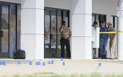 Personnel stand outside a US Navy recruiting building as the area is cordoned off with blue shell casing markers in the parking lot in Chattanooga, Tennessee, on July 16, 2015. (Tim Barber/Chattanooga Times Free Press via AP)