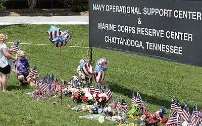 Kelly Caparell, left, and her daughter Keldon Bevel, place several American flags by a makeshift memorial at the entrance to the Naval Operational Support Center and Marine Reserve Center Saturday, July 18, 2015, in Chattanooga, Tennessee. (AP Photo/Mark Zaleski)