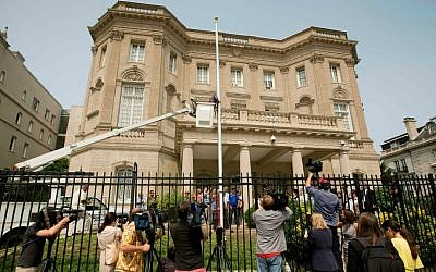 In this June 10, 2015 file photo, members of the media cover workers from Eastern Shores Flagpoles raising a flagpole at the Cuban Interest Section in Washington in preparation for re-opening of embassies in Havana and Washington. (AP Photo/Pablo Martinez Monsivais, File)