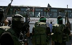 Illustrative: Hamas members watch as a bus carrying Palestinian prisoners arrives at the Rafah crossing with Egypt in the southern Gaza Strip on October 18, 2011. (Abed Rahim Khatib/Flash 90)