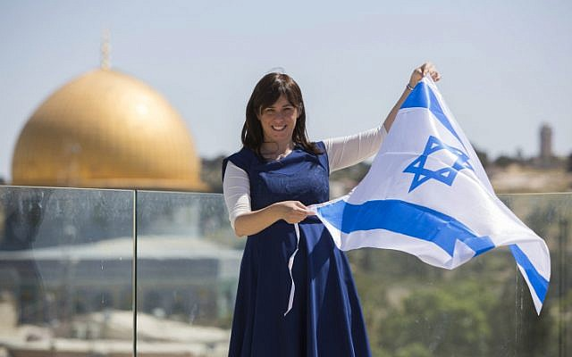 From a vantage point near the Temple Mount, Tzipi Hotovely waves the Israeli flag, with the Dome of the Rock in the background, May 1, 2014. (Yonatan Sindel/Flash90)