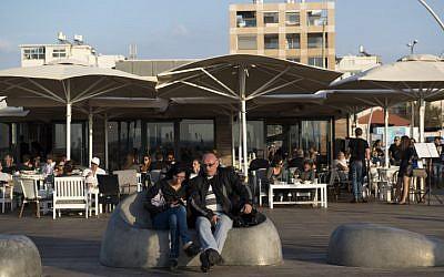 An Israeli couple sits at the Tel Aviv port boardwalk on November 15, 2014. (Danielle Shitrit/Flash90)
