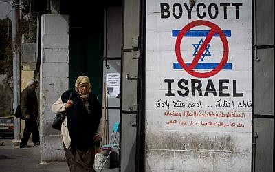 A Palestinian woman walks by a sign calling to boycott Israel in the West Bank city of Bethlehem on February 11, 2015. (Miriam Alster/Flash 90)