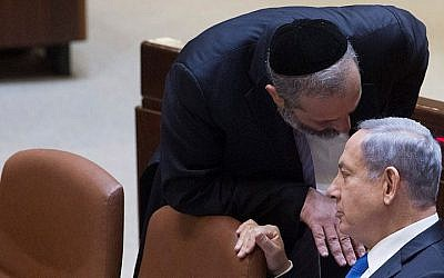 Prime Minister Benjamin Netanyahu speaks with Shas leader and then-economy minister Aryeh Deri in the Knesset on June 17, 2015. (Miriam Alster/Flash90)