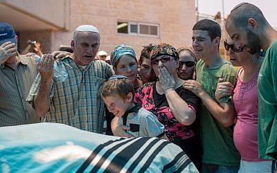 The family of Malachy Moshe Rosenfeld mourns near his body during his funeral at Kochav Hashahar in West Bank, July 01, 2015. (Yonatan Sindel/FLASH90)