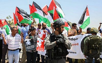Palestinian protesters block a road leading to the Adam settlement in the West Bank, during a demonstration to mark the first anniversary of the killing of 16-year-old Palestinian Mohammed Abu Khder, July 2, 2015. (Flash90)