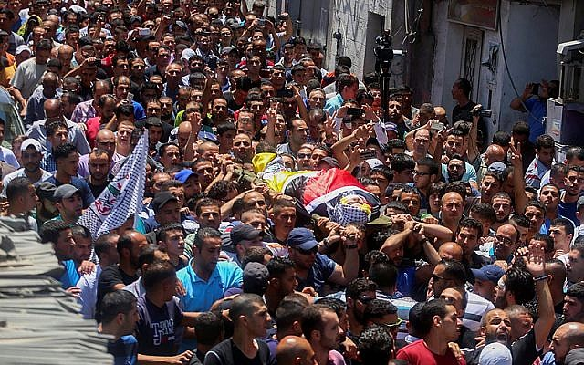 Mourners carry the body of Palestinian youth Mohammed Sami al-Kasbeh, 17, during his funeral in Qalandiya refugee camp, near the West Bank city of Ramallah July 3, 2015. (Flash90)