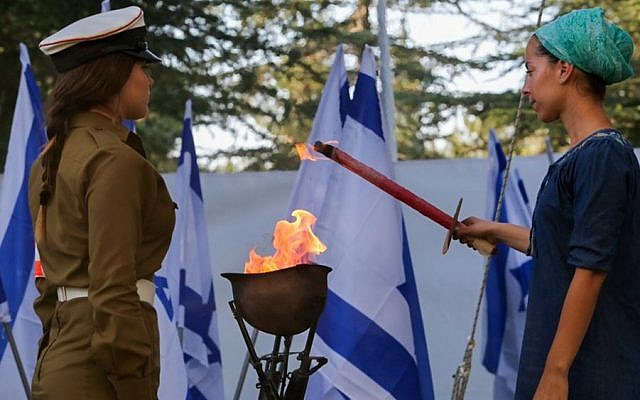 Adi Kaplan, widow of Captain Zvi (Zvika) Kaplan killed in Operation Protective Edge, lights a torch during a ceremony marking one year since the war at the Mount Herzl military cemetery in Jerusalem on July 6, 2015. (Gili Yohanan/POOL/Flash90)