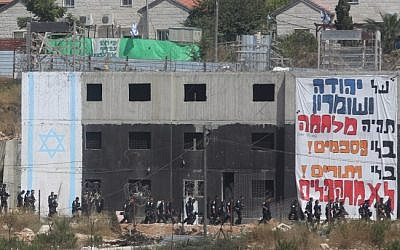 Israeli security forces walk by a building in which Israeli settlers had barricaded themselves to resist an evacuation at the Jewish settlement of Beit El, near the West Bank town of Ramallah on July 28, 2015. (Flash90)