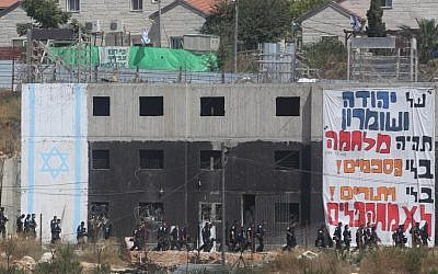 Israeli security forces walk by a building in which Israeli settlers had barricaded themselves to resist an evacuation at the Jewish settlement of Beit El, near the West Bank town of Ramallah, July 28, 2015. (FLASH90)