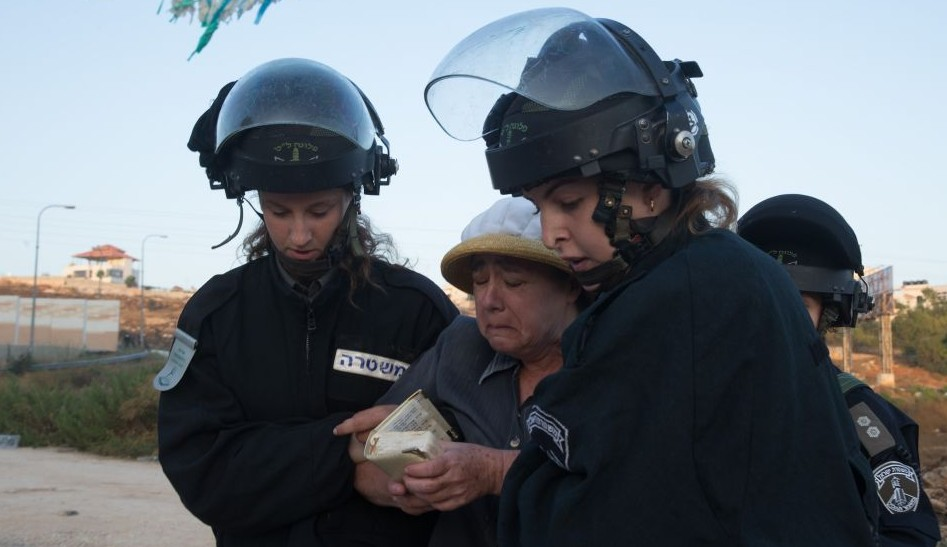Israeli security forces remove a Jewish settler who came to demonstrate against the demolition of two apartment blocks at the Jewish settlement of Beit El, on July 28, 2015 (Photo by Nati Shohat/FLASH90)