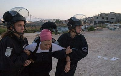 Israeli security forces drag away a Jewish settler who came to demonstrate an evacuation at the Jewish settlement of Beit El, near the West Bank town of Ramallah, July 28, 2015 (Nati Shohat/FLASH90)