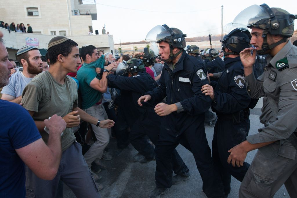 Israeli security forces scuffle with settlers who had barricaded themselves in an attempt to prevent the demolition of illegally constructed buildings, at the Jewish settlement of Beit El, near the West Bank town of Ramallah, on July 28, 2015. (Nati Shohat/FLASH90)