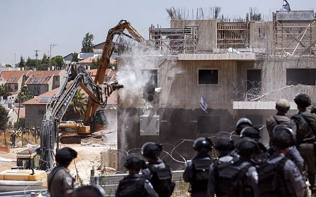 Pictured: Israeli security forces watching as a tractor begins to demolish two buildings in the Israeli settlement of Beit El, near the West Bank city of Ramallah, July 29, 2015. (Yonatan Sindel/FLASH90)demolish two buildings in the Israeli settlement of Beit El, near the West Bank city of Ramallah, July 29, 2015. (Yonatan Sindel/FLASH90)