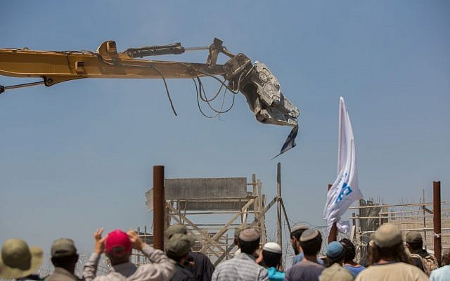 A tractor grabs an Israel flag as it tears down homes in the Beit El settlement July 29, 2015. (Yonatan Sindel/Flash90)