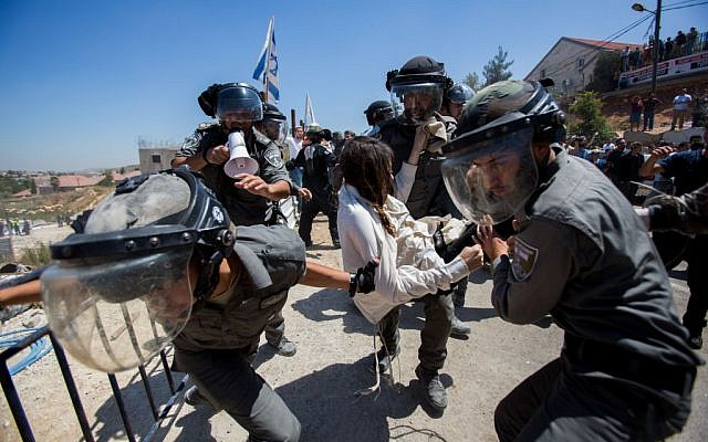 Israeli security forces scuffle with Jewish settlers in the Israeli settlement of Beit El, near the West Bank city of Ramallah, on July 29, 2015, following the High Court's decision to upheld an earlier order to demolish two buildings in the settlement. (Yonatan Sindel/Flash90)