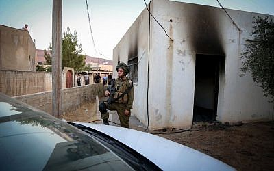 An Israeli soldier stands near a house in the Palestinian village of Duma, near Nablus, where a Palestinian infant was killed July 31, 2015, in an arson attack, apparently by Jewish extremists. (Photo by FLASH90)