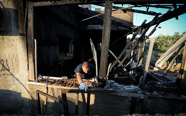 """Israeli security forces seen at a house in the Palestinian village of Duma, near Nablus, where a Palestinian infant was killed July 31, 2015, in an arson attack, apparently by Jewish extremists. Two homes in Duma, were set on fire, and the Hebrew words """"revenge"""" and """"long live king messiah"""" were spray-painted on their walls, alongside a Star of David. (Photo by FLASH90)"""