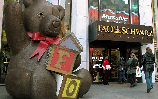 In this Nov. 10, 2003 file photo, customers pass a statue of a teddy bear and a doorman dressed as a toy soldier as they enter the FAO Schwarz on Fifth Avenue in New York. The store is closing its doors for good on Wednesday, July 15, 2015, though it may reopen elsewhere in midtown Manhattan. (AP Photo/Rich Kareckas, File)