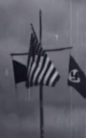 Three flags are flown during a 25-minute film taken at a Nazi youth camp in the United States in 1937: the camp emblem, the American flag, and the swastika. (YouTube screenshot)