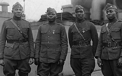 Officers of the United States Army's segregated 366th Infantry Regiment on board the Aquitania, en route home from World War I service. Left to right: Lieutenant C.L. Abbot, South Dakota; Captain Joseph L. Lowe, Pacific Grove, California; Lieutenant Aaron R. Fisher, Lyles, Indiana, recipient of Distinguished Service Cross; Captain E. White, Pine Bluff, Arkansas (Wikimedia Commons/Public domain)