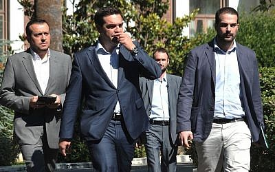 Greece's Prime Minister Alexis Tsipras, center, leaves after a meeting with Greek political party leaders as Minister of State Nikos Pappas, left, and Government spokesman Gabriel Sakellaridis, right, follow him in Athens, Monday, July 6, 2015.  (AP/Angelos Christofilopoulos)